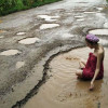 Thai woman takes bath in pothole to protest bad condition of her hometown's roads